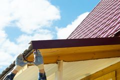 Roof repair by a master against a blue sky background stock photography