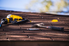Roof repair. Roof shingle repair with nail gun and hummer stock photography