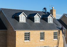 Roof repairs being carried out with ladders Royalty Free Stock Images