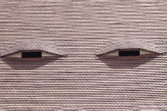 Roof's eyes. In Sibiu, Romania the old houses have window eyes on the roofs Stock Photo