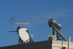 Roof with a satellite dish, TV aerial, hot water solar panel , & air conditioner Royalty Free Stock Photos