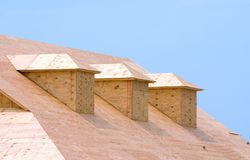 Roof sheeting. New building under construction showing plywood roof sheeting and three dormers Royalty Free Stock Photos