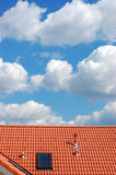 Roof and Sky. Red roof with chimney and window againsta the cloudy sky Stock Images