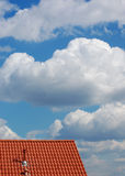 Roof and Sky. Red roof with chimney against the cloudy sky Royalty Free Stock Photo