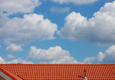 Roof and Sky. Red roof with chimney against the cloudy sky Royalty Free Stock Images