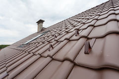 Roof with skylight, natural red tile and chimney with snow stopers Royalty Free Stock Images