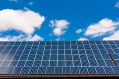 Roof with solar panels. Solar panels on roof with blue sky and white clouds Royalty Free Stock Photo