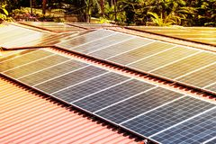 Roof with solar panels fragment under sunny blue sky. Sun is shining on black solar panels. Alternative energy source. Electrification in the Andaman Islands Royalty Free Stock Image