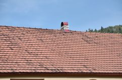 The roof of this square ceramic tile is red. The old type of roof covering in rich houses of the 19th century stock images