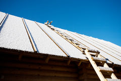 Roof with staircase covered by snow. Roof of village house with staircase covered by snow closeup on blue sky background Royalty Free Stock Image