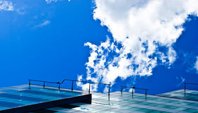 Roof of a tall building. The roof of a tall building against the blue sky with a railing at the Stock Images