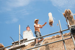 Roof thatchers at work. Catching a bundle of reeds being throw from below, ready to lay on the roof Royalty Free Stock Image