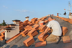 Roof tile installation. Roofing: construction worker on a roof covering it with tiles - roof renovation: installation of tar paper, new tiles and chimney Royalty Free Stock Images