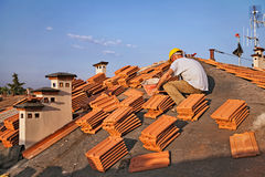Roof tile installation. Roofing: construction worker on a roof covering it with tiles - roof renovation: installation of tar paper, new tiles and chimney Stock Photo