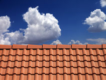 Roof tiles against blue sky. With clouds Royalty Free Stock Image