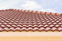Roof tiles and rain gutter horizontal view against blue sky Stock Images