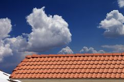Roof tiles, snowy slope and blue sky Stock Photo