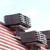 Roof tiles stacked in piles on wooden battens Stock Photo