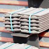 Roof tiles stacked in piles on wooden battens Royalty Free Stock Image