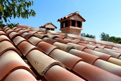 Roof tiles in various decorative shade of red with two small chimneys surrounded with tree branches and clear blue sky background. On warm sunny day stock photo