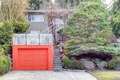 Roof top deck over garage. Clapboard siding house on a hill. Red door garage with roof top deck over it Royalty Free Stock Image