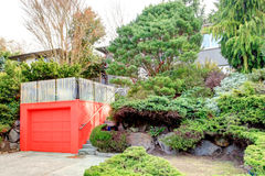 Roof top deck over garage. Clapboard siding house on a hill. Red door garage with roof top deck over it Stock Images