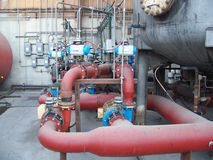 Roof Top Mechanical Area. Mechanical Room on a Roof top Rusty pipelines providing water to and from the business building. Large red pipelines and gray tanker stock image