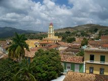Roof Tops II. Roof tops taken in a small town in Cuba.Mountains in the back ground and blue skies, Church bell tower in the distance Royalty Free Stock Image