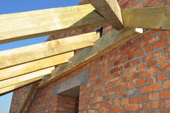 Roof-trusses. Close up on installation of wooden beams at construction the roof truss system of the house. Roofing Construction. Royalty Free Stock Images