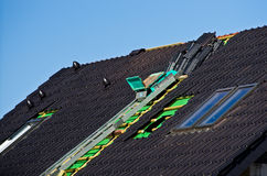 Roof under construction. Detail of the roof under construction with black rooftiles unfinished and windows installed Royalty Free Stock Images