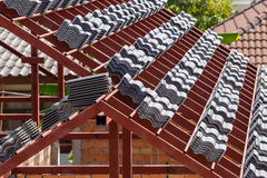 Roof under construction with stacks of roof tiles for home build Royalty Free Stock Photos