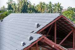 Roof under construction with stacks of roof tiles for home build Stock Photo