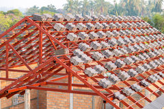 Roof under construction with stacks of roof tiles for home build Stock Photos