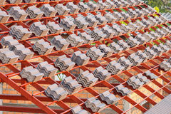 Roof under construction with stacks of roof tiles for home build Stock Images