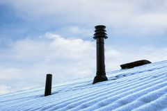 Roof with ventilation pipe and flue terminal in winter Stock Image
