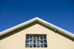 Roof of warehouse. Part of a wooden roof with window as detail of a warehouse in front of blue sky background Royalty Free Stock Image