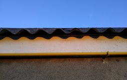 A roof of wavy slate against the blue sky and a yellow gas pipe, attached to a white wall. dark and light stripes. royalty free stock photography