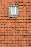 Roof window. Small roof window in a tiled roof Royalty Free Stock Photo