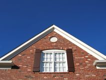 Roof, Window & Sky. A brick house roof with a nice window, wood shutters and blue sky Stock Photography