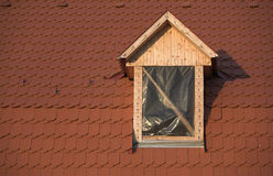 Roof and window, under construction. Wooden window frame and red roof under construction Royalty Free Stock Photos