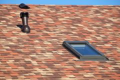 Roof window and ventilation tube on house roof covered with motley soft shingles under blue sky royalty free stock photography