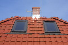 Roof windows, clay tiles, chimney and lightning Royalty Free Stock Photography