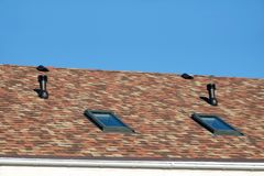 Roof windows and ventilation tubes on house roof covered with motley soft shingles closeup view royalty free stock photography