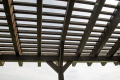 Roof of wooden arbor against the white sky. Modern classical design garden pergola arbor made of wood Royalty Free Stock Photos