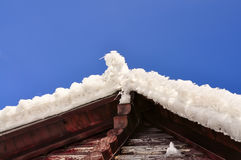 Roof wooden house made of logs covered with snow and icicles Royalty Free Stock Photography