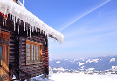 Roof wooden house made of logs covered with snow and icicles Stock Images