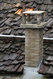 Roof of wooden shingles and stone chimney royalty free stock images