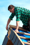 Roof worker. On top of a new house, installing side tiles Stock Image