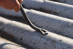 Roof worker repair dangerous asbestos old roof tiles. Royalty Free Stock Photography