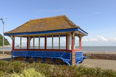 Roofed blue bench at Minehead, Somerset. View of a gazebo built on a blue  bench on seaside promenade at historic touristic village of  Somerset. Shot in bright Stock Images